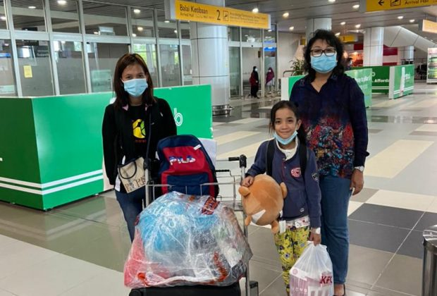 caption: Cheerful...Evelyn gives a beaming smile at the KKIA upon her arrival with her mother, Floryna (left) from Kuala Lumpur after undergoing a successful corrective heart surgery. Standing next to her is Eva, the vice president of SOSHF.